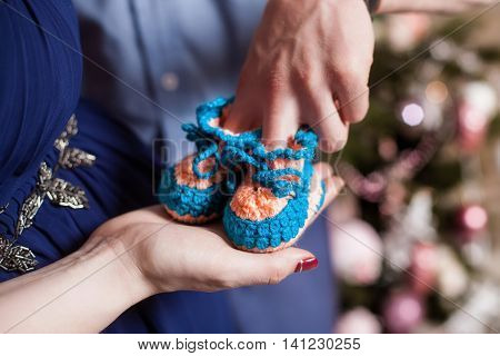 Cute small blue knitted baby booties on hands. Pregnancy concept