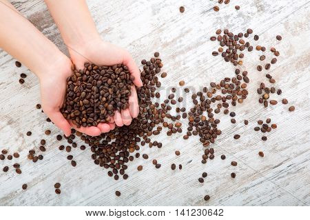 A woman holding coffee beans at a table.