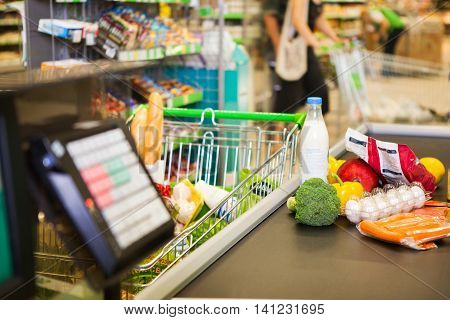 Buying products in supermarket. Cashdesk in store