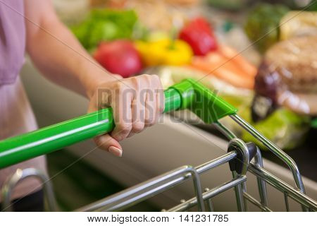 Closeup of woman with shopping cart in grocery store
