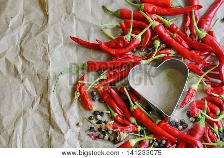 Aluminum heart shapes filled with little chili peppers on vintage paper background. Concept of hot love and passion