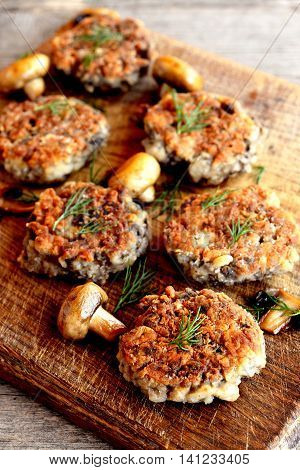 Delicious fried mushroom patties on a wooden cutting board. Beautiful serving mushroom vegetarian patties. Homemade cooked food