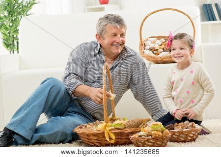 Grandfather and granddaughter sitting on a carpet in the living room next to woven baskets with pastries.