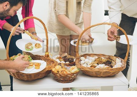 Close-up woven baskets full of baked goods to which a bunch of hands reaching out to take the delicious pastry.