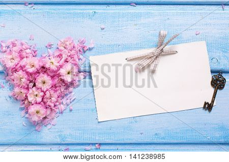 Background with heart from pink flowers and petals empty tag and vintage key on blue wooden planks. Selective focus. Place for text.
