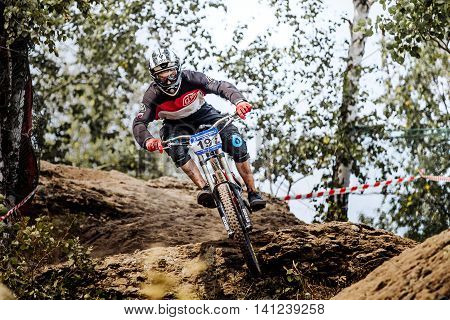 Magnitogorsk Russia - July 23 2016: male athlete competitor downhill rides in forest during National championship downhill