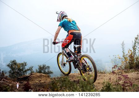 Magnitogorsk Russia - July 23 2016: girl extreme athlete on bike at top of mountain during National championship downhill