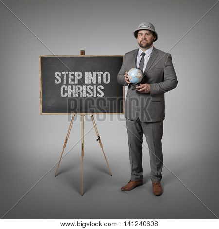 Step into chrisis text on blackboard with businessman holding globe in hands