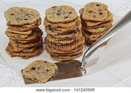 Homemade chewy cookies with chocolate chips and kitchen spatula on baking paper and white background