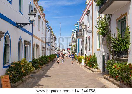 PUERTO DE MOGAN, GRAN CANARIA, SPAIN - APRIL 21, 2016: Pedestrian alley in the harbor area of Puerto de Mogan, a small fishing port on Gran Canaria, Spain. It's called a Little Venice of the Canaries