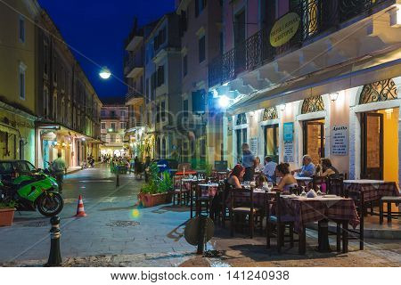 Corfu, Greece - July 12, 2011: Native People And Tourist Walking On The Streets Of City At Night