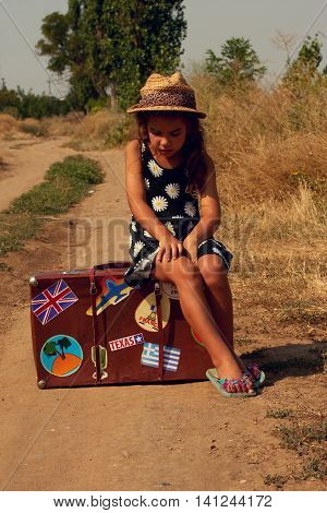 Little girl with suitcase in which the stickers from various countries waiting at the road passing trucks to get hitchhiking