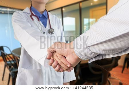 Woman doctor or physician shaking hands with colleague in meeting room
