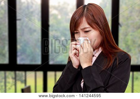 Businesswoman with allergy or cold sneezing into napkin in room - health concept