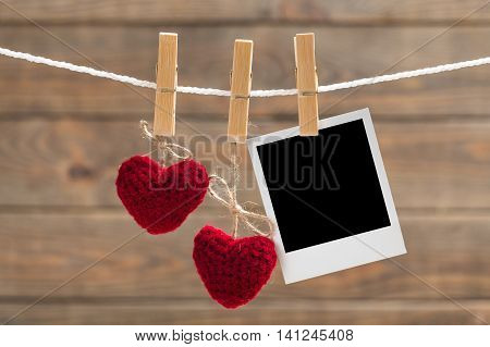 Blank instant photo and two red glass hearts hanging on the clothesline