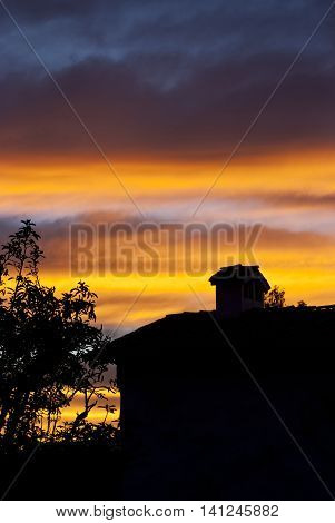 A small House and tree at sunset