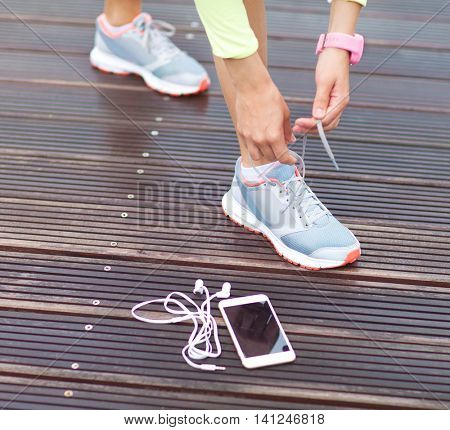 Active runner girl with smartphone and and headphones, tying running shoes laces. Healthy lifestyle, fitness, sport, training, technology concept. Female athletes exercising.