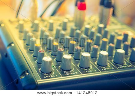 Music mixer desk with various knobs ( Filtered image processed vintage effect. )
