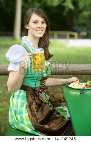 young bavarian woman in dirndl sitting outdoors holding a beer mug
