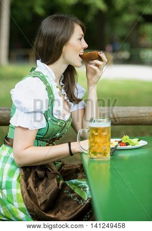 young woman in dindl sitting at beer garden outdoors and eating bread
