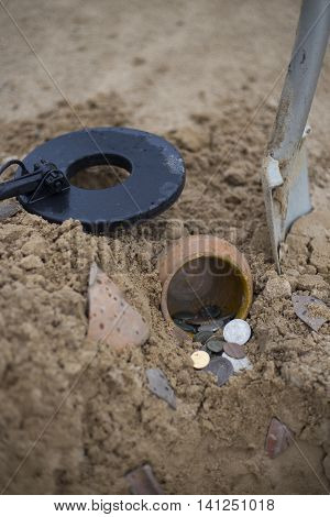 Pot of gold coins collected with help of metal detector, green grass background.