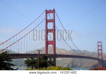 The iconic Golden Gate bridge with the Marin Hills in the background against a blue sky in San Francisco California.