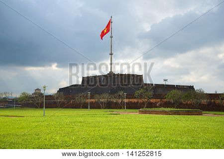 Old main Bastion of the fortress city of Hue with waving national flag. Vietnam
