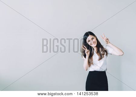 Cute asian university girl doing funny rabbit pose copy space on gray wall background