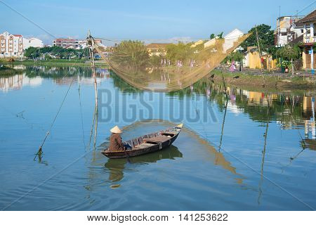 HOI AN, VIETNAM - JANUARY 04, 2016: The fisherman on the boat with fishing net on the Thu Bon river in the early morning. Tourist landmark of the city Hoi An, Vietnam
