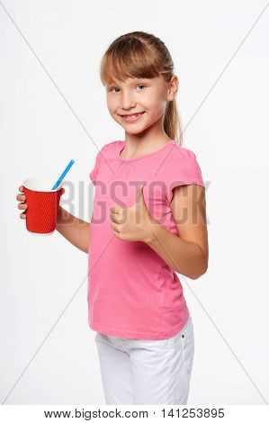 Little child girl holding a drink in disposable paper cup and gesturing thumb up, isolated over gray background, with copy space