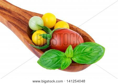 Tomatoes on wooden spoon with basil leaf fresh vegetables cooking concept