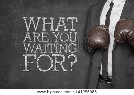 What are you waiting for on blackboard with businessman wearing boxing gloves