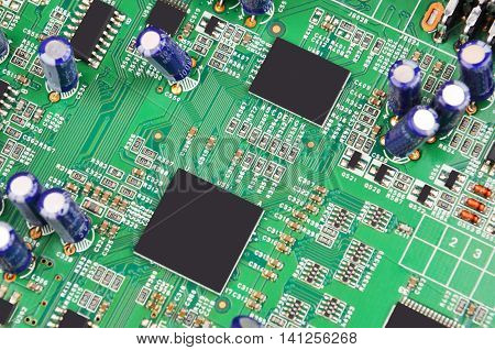 Green printed computer motherboard with microcircuit close-up