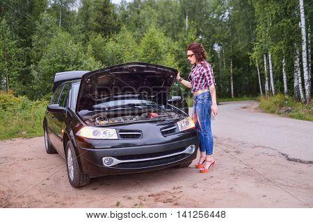 Very sad woman in front of broken car's engine.