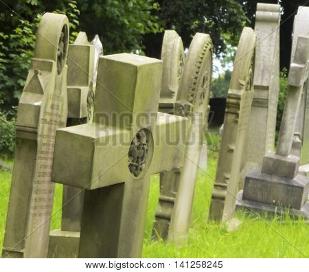 A Stone Cross Leans with the Other Headstones in a Church Graveyard