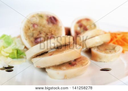 squid stuffed with prepared stuffing and baked. photographed in the studio on a white plate.