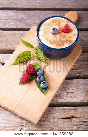 Few Red And Blue Berries On Chopping Board With Creamy Dessert