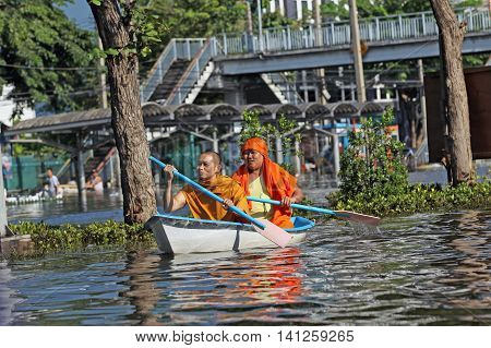 editorial photo of two Buddhist monks floating in a boat on a flooded street in Bangkok Thailand in 2011