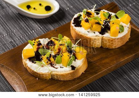 Bruschetta With Chopped Mango, Cress, Basil And Goat Cheese On Fresh Baguette