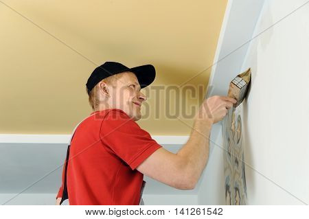Worker adhesive arras. The hand of man holding a brush and put glue on the wall.
