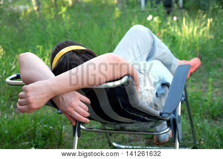 Woman lying down on folding deck chair on a meadow on vacation on a sunny summer day view from the back closeup