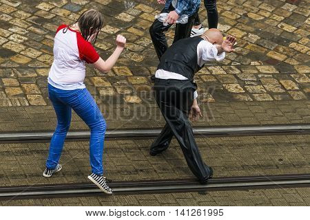 Lviv Ukraine - May 2 2016: Celebration pouring water on Monday after Easter by the town hall. Bald men dance with wet girl