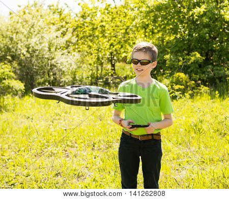Happy boy playing with flying drone with camera controlled by smartphone. Kid with quadcopter drone outdoors.