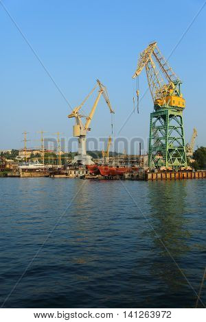 large shipyard with cranes and piers on the coast