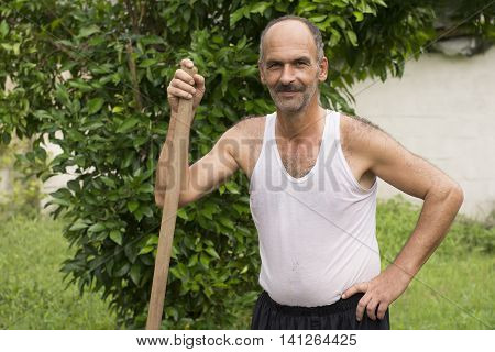Gilan Province- North of IRAN-July 30 2016 Farmer Posed in Front of Tree with Hoe Handle