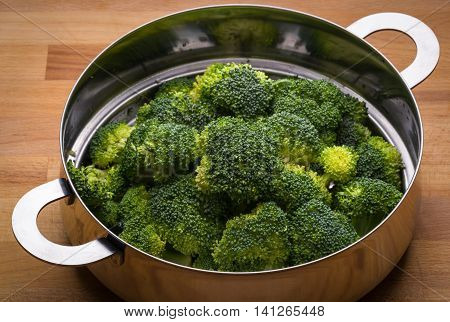Fresh broccoli in stainless steel colander on a wood surface