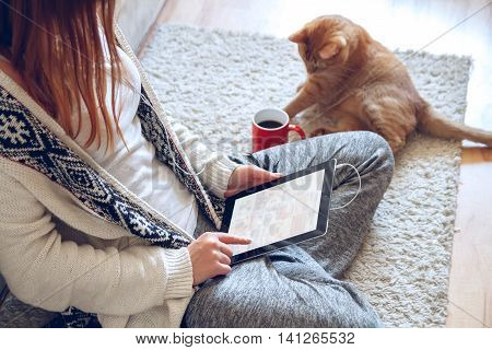 Woman in home cozy clothes sitting on the carpet near the sofa using a tablet with headphones, drinking coffee from a red cup. Next to it lies a thick red cat. Online education concept.