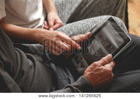 Daughter helps his father to use the tablet. Taught to use the internet while sitting on a sofa. mock up