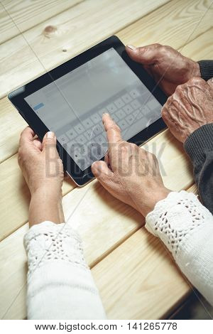 Seniors couple sitting at a wooden table with a tablet in hands.  Online education retirement concept. e-Learning