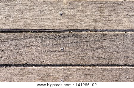 wooden slats with screw horizontally on the beach worn by the sun background